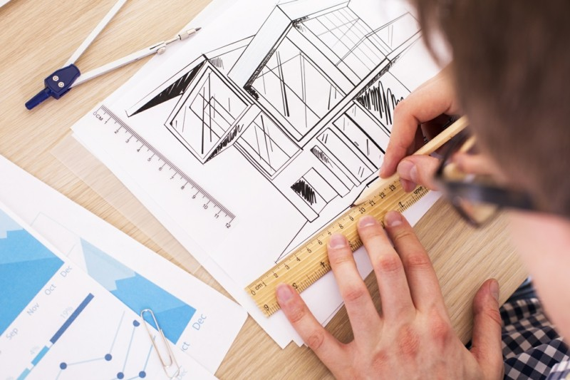 Top view of young architect using ruler and pencil to draw blueprint on wooden desktop with business report and a pair of compasses