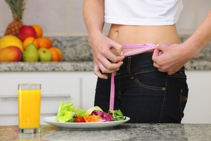 woman eating salad and fruits and measuring her waist